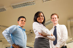 Diverse Business Team Low Angle Ceiling. A diverse business team stands and looks confidently at the camera which is at a low angle Stock Photos