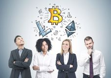 Diverse business team members, blockchain. Diverse business team members brainstorming while standing near a gray wall with cryptocurrency and bitcoin sketches Stock Images