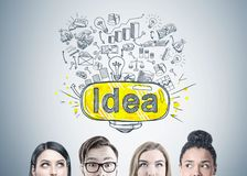 Diverse business team members heads, idea. Heads of members of a diverse business team brainstorming standing near a gray wall with a good idea sketch drawn on Stock Photography