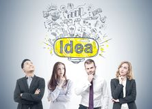 Diverse business team members, idea. Members of a diverse business team brainstorming standing near a gray wall with a good idea sketch drawn on it Stock Image
