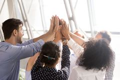 Diverse business team office workers group giving high five toge. Diverse business team associates office workers group giving high five together as concept of stock images