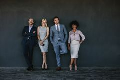 Diverse business team standing together against a wall. Full length portrait of diverse business team standing together against a wall. Group of business men and Stock Photo