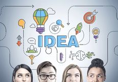 Diverse business team thinking, head, idea. Heads of a diverse business team members. They are brainstorming standing near a gray wall with a bright idea sketch Royalty Free Stock Images
