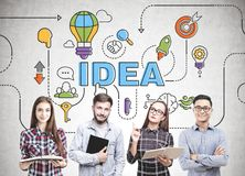Diverse business team thinking, idea. Members of a diverse business team brainstorming standing near a concrete wall with a bright idea sketch drawn on it Royalty Free Stock Photos