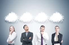Diverse business team, thought clouds, gray. Members of a diverse business team are standing near a gray wall and thinking. There are thought clouds above their Stock Photo