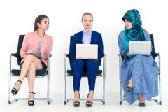 Diverse business woman envy of a caucasian woman in meeting stock image