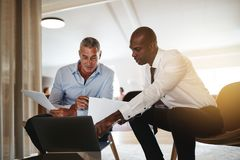 Diverse businessmen discussing work on a laptop in an office royalty free stock images