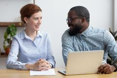 Diverse businesspeople client and consultant talking sitting at. Diverse businesspeople client and consultant sitting at desk during business meeting. Mentor and royalty free stock photos