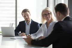 Diverse businesspeople negotiate at business meeting in office. Diverse businesspeople negotiate at office meeting discussing startup project with clients stock photo
