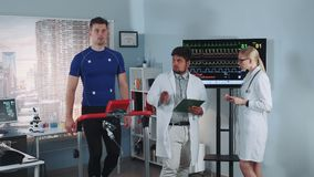 Diverse cardiology technologists speaking about athlete fitness level during the stress test on racetrack. Physical parameters of his body are shown on two stock video footage