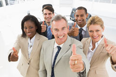 Diverse close business team smiling up at camera giving thumbs up Stock Photography