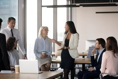 Diverse colleague gathered together in business meeting at cowor. All employees attentive listening young asian female colleague gathered together in business royalty free stock image