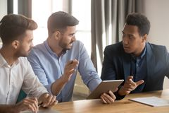 Diverse colleagues discuss business project using tablet stock image