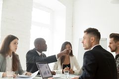 Diverse colleagues disputing during work meeting. Diverse millennial colleagues having disagreement at company meeting, African American worker pointing at stock images