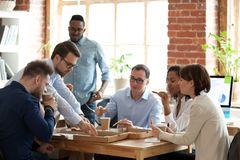 Diverse colleagues enjoy pizza having lunch break in office. Multiracial work team have lunch break at work chat enjoying delicious pizza, diverse colleagues eat royalty free stock image