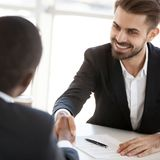 Diverse colleagues handshake closing business deal at briefing royalty free stock image