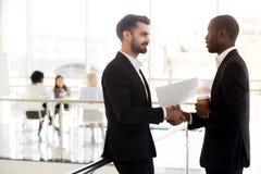 Diverse colleagues handshake in hallway having casual talk stock photos