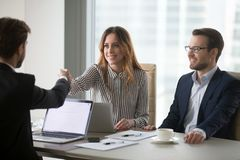 Diverse colleagues shaking hand during business meeting in offic stock images