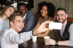 Diverse colleagues smiling for group photo resting in cafe. Diverse colleagues taking group photo on smartphone spending time together in coffeeshop, smiling royalty free stock images