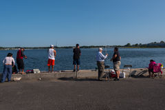 Diverse Collection of People Fishing from a Pier Royalty Free Stock Images