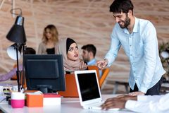 Diverse college students using laptop and talking, learning exchanging ideas royalty free stock photo