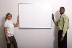 Diverse couple around blank board Stock Photo