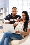 Diverse couple browsing internet at home Royalty Free Stock Photo