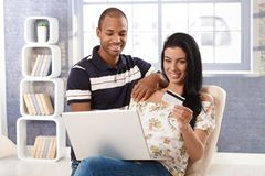 Diverse couple e-shopping at home Stock Images