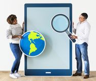 Diverse couple holding a tablet with icons stock photo
