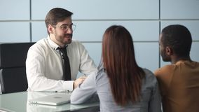 Mortgage broker and diverse couple handshaking ready to make deal