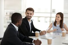 Diverse coworkers chatting during break sitting in conference room. Diverse millennial co-workers chatting take a break during business meeting briefing stock photo