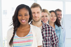 Diverse design team standing in a line smiling at camera Stock Photo