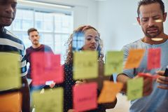 Diverse designers brainstorming with notes on a glass wall stock photo