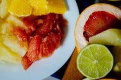 Diverse die citrusvruchten in plakkensinaasappel, citroen, kalk, grapefruit, pompelmoes en een glas jus d'orange worden gesneden stock foto