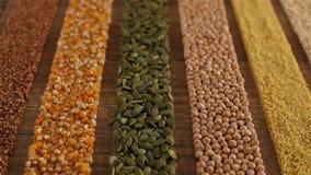 Diverse die zaden en korrels in kleurrijke strepen op de lijst worden geschikt stock footage