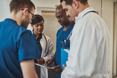 Diverse doctors having an emergency discussion. Diverse group of multiracial doctors having an emergency discussion standing grouped closely together looking at Royalty Free Stock Photography