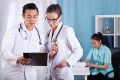 Diverse doctors talking at work Stock Photo