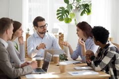Diverse employees brainstorm at business office meeting. Diverse millennial colleagues talk at casual business meeting in office, businessman head briefing with stock photos