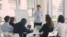 Diverse employees and female coach raise hands at business training