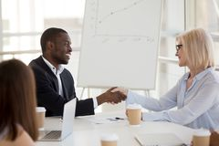 Diverse employees handshake getting acquainted at briefing. Millennial African American worker shaking hand of mature women get acquainted at office briefing stock image