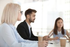 Diverse employees have negotiation at office meeting. Diverse employees sit at table having discussion at business meeting in office, colleagues negotiate in stock photography
