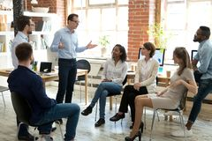 Diverse employees listening to male manager speaking at group meeting. Diverse business team employees listening to male manager coach speaking at group office royalty free stock photos