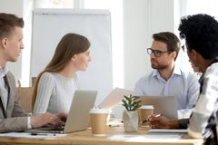 Diverse employees sit at meeting collaborating in office. Millennial diverse employees talk brainstorming or collaborating at office meeting, workers sit at stock photography