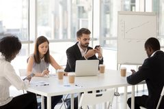 Diverse employees sitting at table using smartphones. Diverse office workers using gadgets sitting at table during business briefing, employees busy with stock images