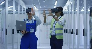 Diverse engineers with laptop in electrical station center. Adult Korean men and black women wearing VR glasses and using laptop while working in hall of solar stock images