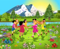 Diverse ethnic group of children having fun together, dancing in a circle in the middle of nature. Surrounded by flowers Royalty Free Stock Photos
