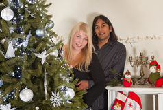 Diverse ethnicity. Couple of divers ethnicity posing at the christmas tree Royalty Free Stock Image