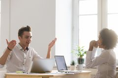 Diverse excited male and female colleagues happy about online. Win, great news or good internet result, african and caucasian project team members celebrating Stock Photos