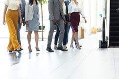 Diverse executives walking in the same direction in hall. Low section of diverse executives walking in the same direction in hall stock photo