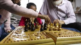 Diverse family playing chess together at home stock footage